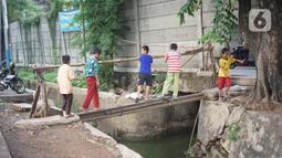 Anak-anak melintasi jembatan saat akan melewati tembok berlubang di Terminal Kampung Rambutan, Jakarta, Kamis (19/12/2019). Jauhnya akses bagi pejalan kaki menjadikan tembok berlubang tersebut pintu alternatif untuk keluar dan masuk Terminal Kampung Rambutan. (Liputan6.com/Immanuel Antonius)