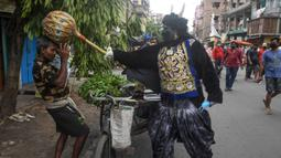 Seorang pria berkostum dewa kematian Yamaraj saat mengimbau warga yang tidak memakai masker di tengah lockdown di Kolkata, India (24/4/2020). Aksinya tersebut sebagai langkah mendukung aturan lockdown India guna mencegah penyebaran wabah pandemi Covid-19 di Kolkata. (AFP/Dibyangshu Sarkar)