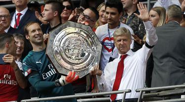 Pelatih Arsenal, Arsene Wenger, bersama kiper Petr Cech, mengangkat trofi Community Shield usai mengalahkan Chelsea di Stadion Wembley, London, Minggu (6/8/2017). Ini merupakan trofi Community Shield yang ke-15 bagi Arsenal. (AFP/Ian Kington)