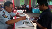 Seorang petugas Lapas Lowokwaru Malang membantu warga binaan memasukkan surat suara usai pencoblosan (Liputan6.com/Zainul Arifin)