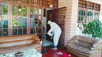Personel Polsek Tampan masuk ke rumah warga terkonfirmasi Covid-19 menyemprotkan disinfektan. (Liputan6.com/M Syukur)