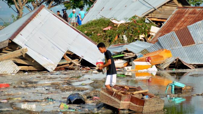 Seorang pria memeriksa kerusakan akibat gempa dan tsunami di Palu, Sulawesi Tengah , Sabtu (29/9). Gelombang tsunami setinggi 1,5 meter yang menerjang Palu terjadi setelah gempa bumi mengguncang Palu dan Donggala. (AP Photo/Rifki)