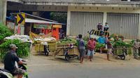 Pedagang Pasar Sayur Kedungrejo Malang tak bisa mengirim sayur ke Surabaya dengan lancar sejak PSBB. Di Kota Batu, aktivitas pengiriman pasar sayur antar kota dikhawatirkan jadi transmisi lokal Corona Covid-19 (Liputan6.com/Zainul Arifin)