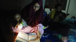 Warga membaca Alquran saat melakukan iktikaf di sebuah masjid di Bandung (6/6). Mereka melakukan iktikaf di masjid dengan mendirikan tenda. (AFP/Timur Matahari)