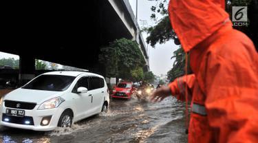 Petugas PPSU mengatur lajur kendaraan saat banjir menggenangi Jalan DI Panjaitan, Jakarta, Senin (3/12). Hujan deras yang mengguyur Jakarta sejak siang tadi menyebabkan banjir menggenangi hingga sebetis orang dewasa. (Merdeka.com/ Iqbal S. Nugroho)