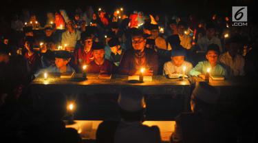 Santri dari Pondok Pesantren  Nurul Hidayah melakukan tadarus alquran dengan penerangan obor di tengah sawah Dusun Tempel, Desa Sempu, Kecamatan Andong, Kabupaten Boyolali, Selasa ( 21/5/2019). Pengajian tersebut untuk menyambut malam Nuzulul Quran pada 17 Ramadan 1440 Hijriah. (Liputan6.com/Gholib)