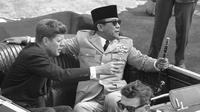Presiden Amerika John Kennedy menunjuk Presiden Republik Indonesia Sukarno saat mereka duduk di mobil terbuka sesaat sebelum berangkat di Pangkalan Angkatan Udara Andrews, Washington, 24 April 1961. (AP Photo)
