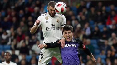 Pemain Real Madrid, Karim Benzema melakukan sundulan saat berebut bola dengan pemain Leganes, Unai Bustinza pada laga leg pertama babak 16 besar Copa del Rey di Santiago Bernabeu, Rabu (9/1). Madrid sukses mengandaskan Leganes 3-0. (AP/Manu Fernandez)