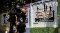Warga berjalan dekat mural imbauan untuk mematuhi protokol kesehatan di Jakarta, Selasa (20/7/2021). Kementerian Kesehatan mencatat pasien COVID-19 di Jakarta yang sembuh pada 19 Juli 2021 sebanyak 12.674 atau meningkat dibandingkan 18 Juli 2021 sebanyak 11.857 orang. (Liputan6.com/Johan Tallo)