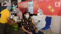 Petugas medis melakukan vaksinasi di vaksin keliling, Jakarta Timur, Minggu (31/07/2021). Bank DKI turut berkontribusi sebagai kolaborator pada 10 unit mobil vaksin keliling dalam program Mobil Vaksin Keliling guna menekan penyebaran Covid-19. (Liputan6.com/HO/Helmi)