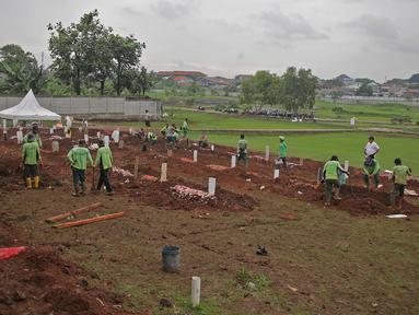 Petugas dengan APD melakukan proses pemakaman dengan protokol Covid-19 di TPU Bambu apus, Jakarta Timur, Minggu (24/1/2021). Empat hari dibuka, 126 jenazah telah dikebumikan dengan protap Covid-19 di TPU Bambu Apus, Cipayung, Jakarta Timur. (Liputan6.com/Herman Zakharia)