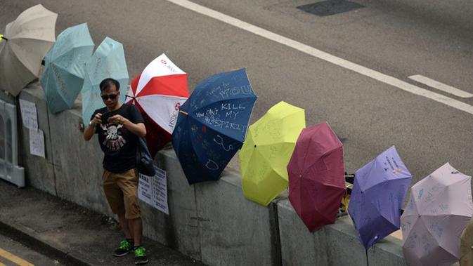 Seorang pria berdiri di dekat payung-payung dukungan pelaksanaan demokrasi langsung di dekat pusat pemerintahan Hong Kong, (2/10/2014). (AFP PHOTO/Dale De La Rey)