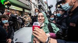 Petugas bantuan Italia Silvia Romano, dikawal Carabinieri, melepaskan masker saat konferensi pers setibanya di rumahnya di Milan, 11 Mei 2020. Terkait keputusan menjadi mualaf, Silvia dengan tegas mengatakan telah bersyahadat selama penculikan dan itu pilihannya tanpa paksaan. (AP/Luca Bruno)