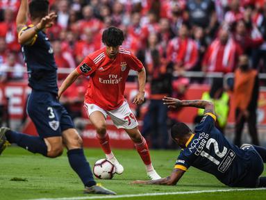 Gelandang Benfica, Joao Felix (tengah) berusaha melewati dua pemain Santa Clara selama pertandingan Liga Portugal di stadion Luz di Porto pada 18 Mei 2019. Pemain 19 tahun ini diboyong Atletico Madrid seharga 126 juta euro atau setara Rp 2 triliun. (AFP Photo/Patricia De Melo Moreira)