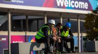 Para pekerja Mobile World Congress (MWC) 2020 duduk di luar lokasi pameran di Barcelona, Spanyol, Kamis (13/2/2020). Penyelenggara MWC 2020, GSMA, batal menggelar pameran telekomunikasi terbesar di dunia tersebut karena ancaman virus corona. (AP Photo/Emilio Morenatti)
