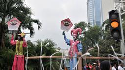 Badut menyosialisasikan sistem tilang Electronic Traffic Law Enforcement (ETLE) kepada pengunjung car free day (CFD) di Bundaran HI, Jakarta, Minggu (25/11). Sistem tilang ETLE menggunakan CCTV berteknologi canggih. (Merdeka.com/Iqbal Nugroho)