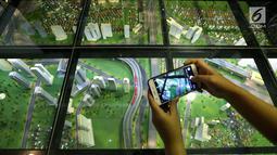 Pengunjung mengabadikan gambar LRT city pada pameran Indonesia Property Expo 2018 di JCC Jakarta, Senin (24/9). Dua anak usaha PT Adhi Karya (Persero) Tbk akan membangun 2.668 unit di LRT City Green Avenue, Bekasi Timur. (Liputan6.com/Fery Pradolo)