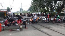 Pengendara motor melintas di perlintasan kereta api yang tidak berpalang pintu di kawasan Roxy, Jakarta, Rabu (21/3). Akhirnya antara warga dan petugas menyepakati untuk membuka celah selebar dua meter di lokasi tersebut. (Liputan6.com/Arya Manggala)