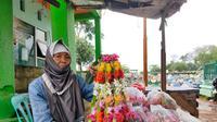 Nuryana, nenek berusia 80 tahun yang masih semangat berjualan kembang kuburan di TPU Kandang Kawat Palembang, kendati di bualn Ramadan sepi pelayat yang datang (Liputan6.com / Nefri Inge)