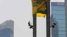 Petugas kepolisian bernegosiasi dengan aktivis lingkungan Green Peace saat membentangkan spanduk di Patung Selamat Datang, Bunderan HI, Jakarta, Rabu (23/10/2019). Dalam aksi yang telah berlangsung selama 13 jam, mereka diamankan petugas yang telah berjaga dibawah. (Liputan6.com/Faizal Fanani)