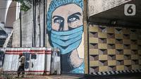 Pejalan kaki melintas dekat lukisan mural melawan COVID-19 di Kawasan Cikokol, Cawang, Jakarta, Minggu (4/10/2020).  Mural masih dianggap menjadi sarana edukasi kesehatan yang tepat bagi warga untuk menjaga diri dari penularan virus Covid 19. (Liputan6.com/Faizal Fanani)
