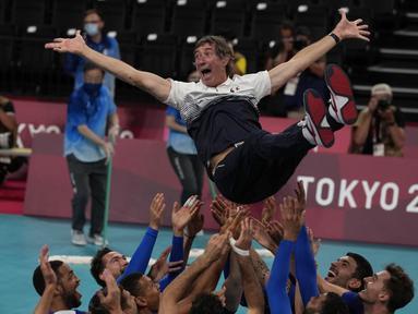 Pemain Prancis melemparkan pelatih kepala Laurent Tillie ke udara saat mereka merayakan kemenangan atas Russian Olympic Committee pada pertandingan final bola voli putra Olimpiade Tokyo 2020 di Tokyo, Jepang, Sabtu (7/8/2021). Prancis mengalahkan ROC 3-2. (AP Photo/Frank Augstein)