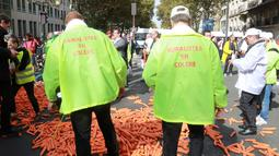 Demonstran membuang sebanyak 1,2 ton wortel ke jalanan depan kantor Kementerian Kesehatan di Paris, Rabu (4/10). Pemerintah ingin meningkatkan kesadaran masyarakat Paris agar berhenti merokok dengan cara menaikan harga rokok. (AFP PHOTO/JACQUES DEMARTHON)