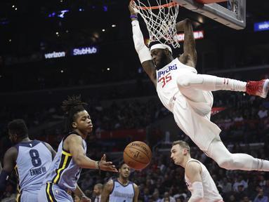 Pemain L. A. Clippers, Willie Reed bergelantungan pada ring usai mencetak poin saat melawan Memphis Grizzlies dalam laga NBA basketball game, di Staples Center, Los Angeles, (2/1/2018). Clippers menang 113-105. (AP/Jae C. Hong)