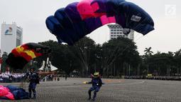 Penerjun wanita dari TNI mendarat saat memeriahkan apel peringatan Hari Kartini 2018 di Silang Monas, Jakarta, Rabu (25/4). Sebanyak 721 personel gabungan prajurit wanita TNI dan Polri beratraksi di hadapan Presiden Jokowi. (Liputan6.com/Johan Tallo)
