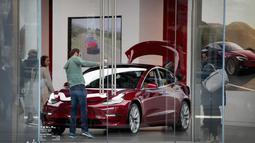 Pengunjung melihat mobil Tesla model 3 di sebuah dealer di Chicago, Illinois (30/3). Produsen mobil listrik Tesla mengkonfirmasi keterlibatan sistem autopilot kendaraannya dalam kecelakaan fatal pada 23 Maret 2018 lalu. (Scott Olson / Getty Images / AFP)