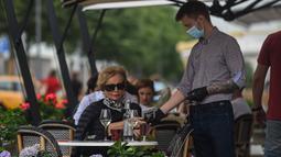 Pramusaji yang mengenakan masker dan sarung tangan melayani pelanggan di sebuah kafe di Moskow, 13 Juli 2020. Rusia melaporkan 6.537 kasus terkonfirmasi baru COVID-19 dalam 24 jam terakhir, sehingga totalnya bertambah menjadi 733.699, pada Senin (13/7). (Xinhua/Evgeny Sinitsyn)