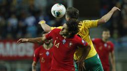 Penyerang Portugal, Goncalo Paciencia berebut bola udara dengan pemain Lithuania, Saulius Mikoliunas pada pertandingan Grup B Kualifikasi Piala Eropa 2020 di stadion Algarve di luar Faro, Portugal (14/11/2019). Portugal menang besar 6-0 atas Lithuania. (AP Photo/Armando Franca)