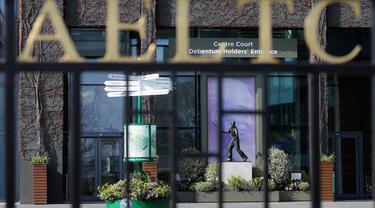 Salah satu pintu masuk utama ke All England Lawn Tennis dan Croquet club dengan latar belakang patung pemenang Wimbledon Fred Perry di London, Rabu (1/4/2020). Turnamen grand slam Wimbledon yang dijadwalkan digelar 19 Juni-21 Juli tahun ini batal karena pandemi virus corona. (AP/Kirsty Wigglesworth)