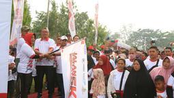 Bupati Mempawah, Erlina (kiri), Direktur Utama Askrindo Andrianto Wahyu Adi (tengah) Direktur Operasional PTPN XIII Ospin Sembiring (kanan) mengibarkan bendera tanda dimulainya jalan sehat  5 KM di Kabupaten Mempawah, Kalimantan Barat, Minggu (18/8/2019). (Liputan6.com/HO/Iqbal)