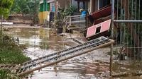 Banjir yang melanda Bojongkukur, Kecamatan Gunungputri, Kabupaten Bogor berangsur-angsur mulai surut dan menyisakan lumpur serta genangan di jalan dan permukiman warga, Minggu (25/10/2020). (Liputan6.com/Achmad Sudarno)