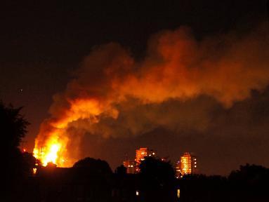 Kepulan asap menyelimuti sebuah apartemen bertingkat 24 lantai yang terbakar di London (14/6). Gedung Grenfell Tower yang terbakar itu berada di kompleks Lancester West Estate. (AFP PHOTO / Jonathan Kelly)