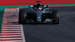Pembalap Mercedes Lewis Hamilton mengendarai mobilnya saat tes pramusim di Sirkuit de Catalunya, Spanyol (6/3). Juara dunia empat kali ini tidak terlalu terkesan dengan Circuit de Catalunya sehabis di renovasi. (AP Photo / Manu Fernandez)