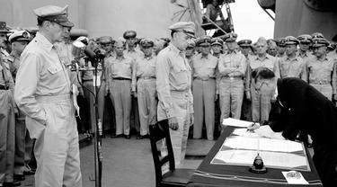 Jenderal AS Douglas MacArthur (kiri) menyaksikan Menteri Luar Negeri Jepang Manoru Shigemitsu menandatangani dokumen penyerahan di atas kapal perang USS Missouri, Teluk Tokyo, 2 September 1945. Penandatanganan ini menandai berakhirnya Perang Dunia II. (AP Photo/C.P. Gorry, File)
