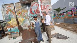 Seniman Teguh Ostenrik (kiri) berbincang dengan Dubes Jerman untuk Indonesia Michael Freiherr von Ungern-Sternberg saat pemasangan pecahan Tembok Berlin dan Patung Menembus Batas di RPTRA Kalijodo, Jakarta, Selasa (26/9). (Liputan6.com/Immanuel Antonius)