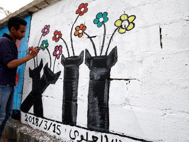 Seorang seniman melukis grafiti pada dinding di Ibu Kota Sanaa, Yaman, Kamis (15/3). Kampanye ini untuk mendukung perdamaian di negara yang terkena dampak perang. (Mohammed HUWAIS/AFP)