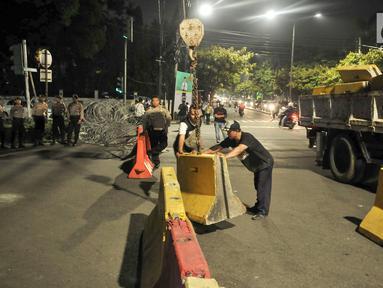 Petugas Dishub DKI dibantu polisi memasang pembatas beton dan kawat berduri di perempatan Jalan Imam Bonjol, Jakarta Pusat, Senin (20/5/2019). Menjelang pengumuman hasil Pemilu 2019 puluhan personel gabungan Polisi dan Brimob juga telah bersiaga di sekitar kantor KPU. (merdeka.com/Iqbal S Nugroho)