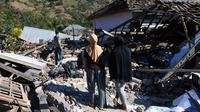 Dua wanita melihat warga menyelamatkan sisa-sisa puing dari rumah yang rusak di Menggala, Lombok Utara, Rabu (8/8). Warga terdampak gempa Lombok mulai mengamankan barang berharga karena kuatir dijarah pihak tidak bertanggung jawab. (AFP/ADEK BERRY)