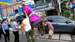 Petugas Suku Dinas Sosial dan Satpol PP Jakarta Selatan merazia pengamen ondel-ondel di kawasan Bulungan, Jakarta, Rabu (24/3/2021). Razia Penyandang Masalah Kesejahteraan Sosial (PMKS) dilakukan untuk ketertiban lingkungan dan terciptanya Ibu Kota yang bebas dari PMKS. (Liputan6.com/Faizal Fanani)