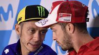 Pebalap Movistar Yamaha, Valentino Rossi, berbincang dengan Andrea Dovizioso saat jumpa pers jelang GP Aragon di Alcaniz, Aragon, Kamis (21/9/2017). Rossi dinyatakan lolos tes medis untuk mengikuti balapan MotoGP Aragon. (AFP/Javier Soriano)