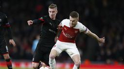 Duel antara Aaron Ramsey dan Benjamin Bourigeaud pada leg kedua,babak 16 besar Liga Europa yang berlangsung di Stadion Emirates, London, Jumat (15/3). Arsenal menang 3-0 atas Rennes. (AFP/Ian Kington)
