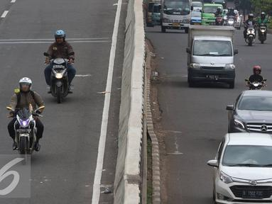 Pengendara motor melintas di Jalan Layang Non Tol Kampung Melayu arah Tanah Abang, Jakarta, Senin (9/1). Minimnya pengawasan membuat pemotor dapat leluasa memasuki jalur khusus roda empat atau lebih tersebut. (Liputan6.com/Immanuel Antonius)