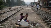 Seorang gadis muda memandikan saudaranya di sebelah jalur kereta api di New Delhi, India, Selasa (16/10). Hasil survei terhadap 104 negara yang dirilis bulan lalu menemukan bahwa sekitar 1,3 miliar orang hidup dalam kemiskinan. (AP Photo/Altaf Qadri)