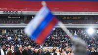 Seorang peserta mengibarkan bendera Rusia saat mendegarkan pidato Vladimir Putin dalam sebuah kampanye di stadion Luzhniki di Moskow (3/3). Putin pun telah bersiap untuk memperoleh periode keempatnya sebagai presiden Rusia. (AFP/Kirill Kudryavtsev)