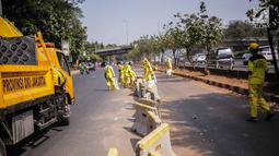 Petugas Dinas Bina Marga DKI Jakarta memperbaiki separator busway di kawasan Jalan Gatot Subroto, Jakarta, Selasa (1/10/2019). Separator busway dirusak massa saat terjadi bentrok antara polisi dengan demonstran di kawasan tersebut. (Liputan6.com/Faizal Fanani)