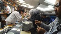 Petugas melayani nasabah di gerai penukaran mata uang di Ayu Masagung, Jakarta, Senin (13/8). Pada perdagangan jadwal pekan, senin (13/08). Nilai tukar rupiah terhadap dolar AS menyentuh posisi tertingginya Rp 14.600. (Merdeka.com/Arie Basuki)
